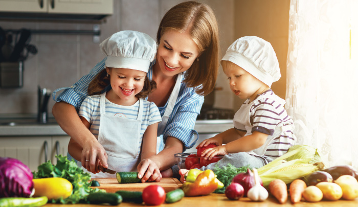 Mother with two young children helping to prepare a meal in the kitchen All three smiling